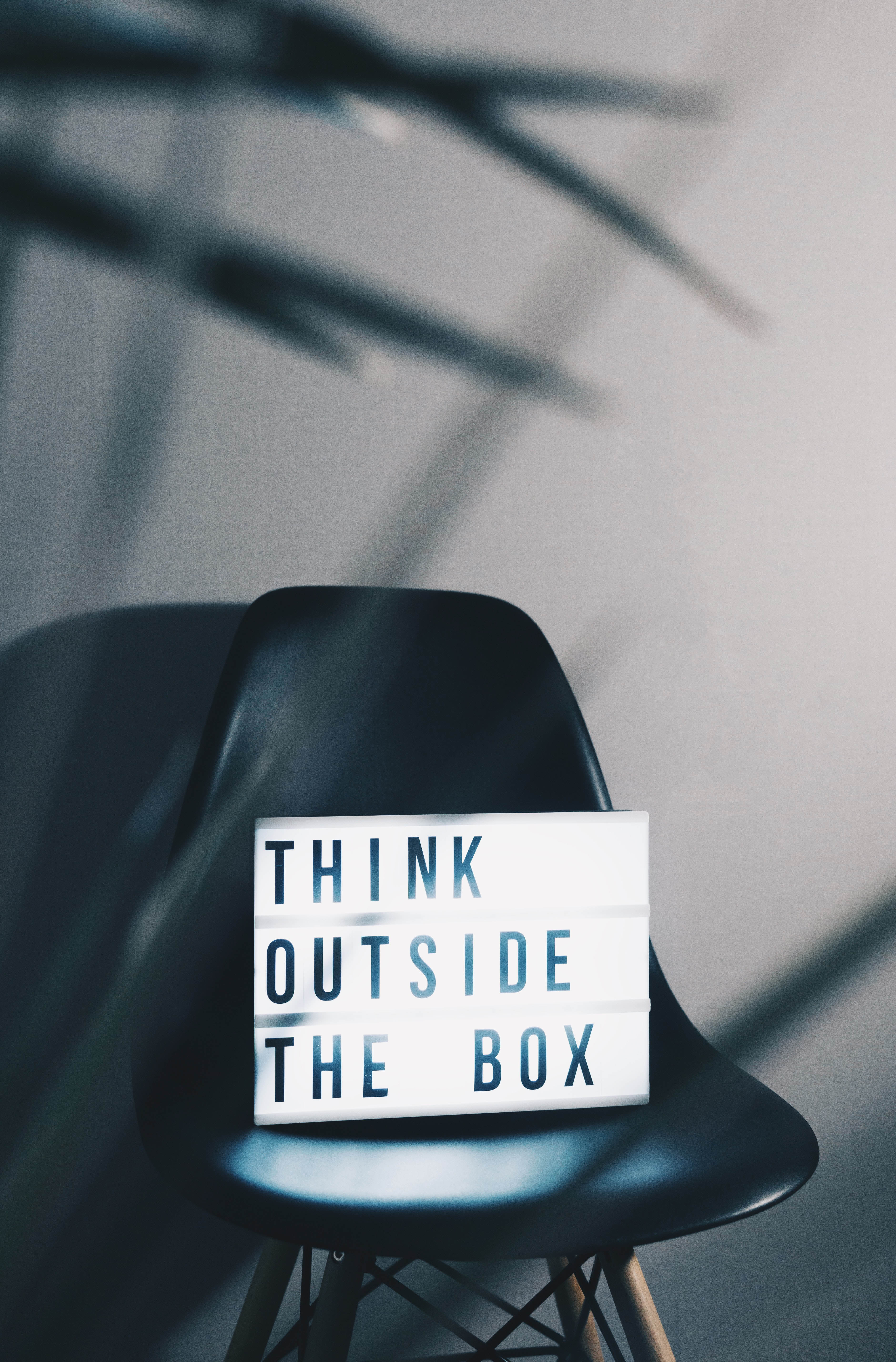 Think outside the box written on lightbox which sits on a black chair
